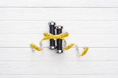 Close-up view of dumbbells and yellow measuring tape. On wooden surface royalty free stock image