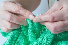 Elderly woman hands who knits a green sweater. Close up view of a elderly woman hands who knits a green sweater Royalty Free Stock Photos