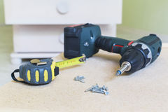 Close-up view of electric screwdriver, screws & tape ruler Stock Photos