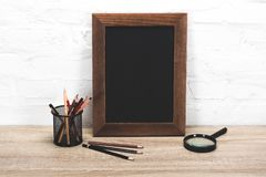 Close up view of empty photo frame, magnifying glass and office supplies. On table stock photos