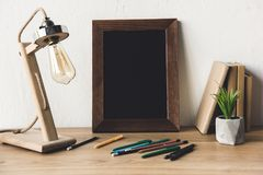 Close up view of empty photo frame, table lamp and office supplies. On table royalty free stock image