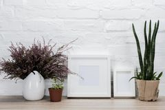 Close up view of empty photo frames and flowers. On wooden tabletop royalty free stock photos