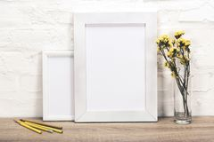 Close up view of empty photo frames, pencils and flowers in vase. On wooden surface royalty free stock photos