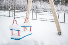 Close up view of empty swings in the city street on a winter snowy day stock photo