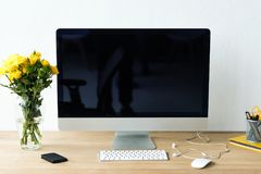 close up view of empty workplace with blank computer screen, keyboard, computer mouse and bouquet of chrysanthemum flowers stock image