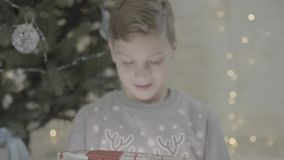 Close up view on excited happy boy kid opening christmas present gift box surprised in awe sitting near new year tree. Close up view on happy excited kid boy stock footage