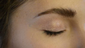 Close up view on eye of beautiful model getting makeup with eyeshadow. stock footage