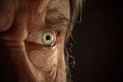Close-up view on the eye of senior man. Close-up view on the screwed-up eye of senior or mature man. Elderly caucasian model. Gray angry eye with red veins. Old Royalty Free Stock Photo