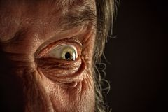 Close-up view on the eye of senior man. Close-up view on the screwed-up eye of senior or mature man. Elderly caucasian model. Gray angry eye with red veins. Old Royalty Free Stock Photos