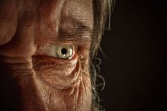Close-up view on the eye of senior man. Close-up view on the screwed-up eye of senior or mature man. Elderly caucasian model. Gray angry eye with red veins. Old Stock Images