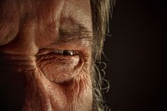Close-up view on the eye of senior man. Close-up view on the screwed-up eye of senior or mature man. Elderly caucasian model. Gray angry eye with red veins. Old Stock Photos