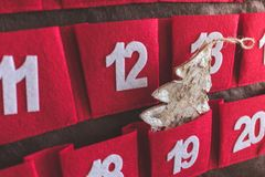 Close up view of a red and brown textile Advent calendar with dates and a Christmas tree decoration in a pocket stock image