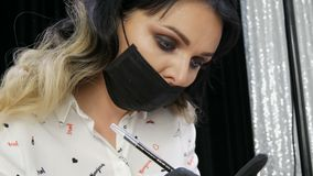 Close-up view of the face of young beautiful stylist woman beautician in black medical mask. stock video