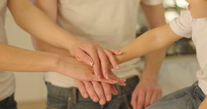 The close-up view of the family hands putting them on each other. The symbol of team unity. The close-up view of the family hands putting them on each other stock video footage
