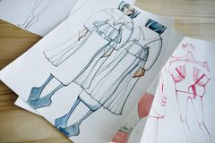 Fashion sketches. Close-up view of fashion sketches on wooden table stock photo