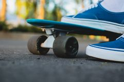 Penny skateboard commute hipster transport solutions. Close-up view of the feet in the blue canvas skate shoes standing at the blue plastic skateboard outdoor Royalty Free Stock Image