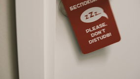 Close-up view of female coming into her room in hotel and puts on the knob the door hanger, asking do not disturb her. stock footage