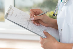 Close-up view of female doctor hands filling patient registratio Stock Photos
