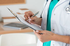 Close-up view of female doctor hands filling patient registratio Stock Images