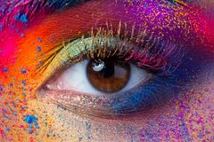 Close up view of female eye with bright multicolored fashion mak. Eup. Holi indian color festival inspired. Studio macro shot royalty free stock images