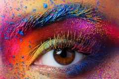 Close up view of female eye with bright multicolored fashion mak. Eup. Holi indian color festival inspired. Studio macro shot Stock Photography