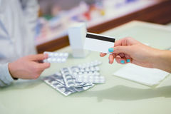 Close-up view of female hand holding credit card and pharmacist Royalty Free Stock Image