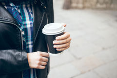 Close-up view of female hands with beautiful natural manicure holding cup of take away coffee. Copy-space blank for advertisement content. Street background Stock Image