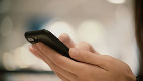 Close-up view of female hands holding smartphone, using the touchscreen technology. Young woman typing on the screen. Girl surf the Internet from cellphone stock footage