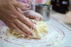 Close-up view of the female hands kneading dough for homemade potstickers. Motion blur. Close-up view of the female hands kneading dough for potstickers. Motion Royalty Free Stock Photos