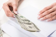 Female hands putting dollar banknotes in envelope. Close-up view of female hands putting dollar banknotes in envelope Stock Photo