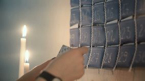 Close-up view of female hands taking out card from advent calendar with gifts and reading the Christmas congratulation. stock footage