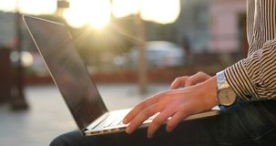 A close-up view of female hands typing on a notebook. Stylish business outfit with a watch and a sunset on a background. stock video