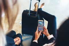 Close-up view of female holding smartphone with different applications on screen sitting with her legs resting on her Royalty Free Stock Photos