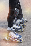 Close-up view of female legs and male legs in roller blades Stock Photos
