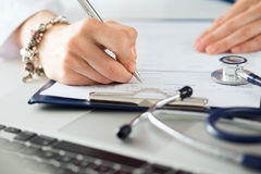 Close up view of female medicine doctors hands filling patient m royalty free stock photography