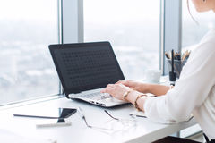 Close-up view of a female office worker typing, working with new project at her workplace, using laptop and wi-fi Royalty Free Stock Photography