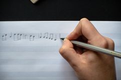 Music notes writing composer creating musician art. Close-up view of the female`s hand writing music notes in the empty sheet music. The concept of the music royalty free stock images