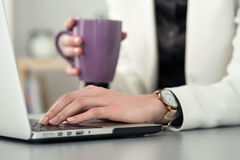 Close up view of female student at workplace holding cup of tea Royalty Free Stock Photos