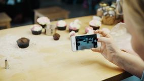 Close-up view of female taking photos of cupcakes with she has baked. Young woman using the camera on smartphone. Blonde housewife cooking in the kitchen stock footage