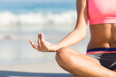 Close up view of fit woman doing yoga beside the sea Royalty Free Stock Image