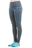 Close up view of fit woman legs wearing colourful striped sports trousers and blue socks from side view in standing foot to foot p Royalty Free Stock Image