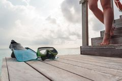 Flippers and mask on a pier with woman legs descending the stairs. cloudy sky as background stock images