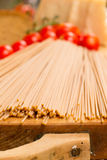 Close up view of foreground look - spaghetti pasta on wooden surface and tomatoes on the background Stock Photography