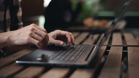 Freelance Man Typing on the Laptop. Close up view of freelance man typing on the laptop while sitting at the wooden table at the cafeteria stock footage