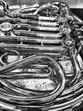 Close-up view of a French Horn. Close up view of a silver double French Horn with music underneath Royalty Free Stock Photos