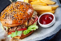 Close up view on fresh big burger served with sauce and French fries. Traditional american fast food. Juicy cheeseburger with stock photography