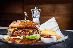 Close up view on fresh big burger served with sauce and French fries. Traditional american fast food. Juicy cheeseburger with stock photos