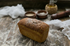 Close up view of fresh brown crispy loaf of bread lying on the wooden table sprinkled with flour.  Stock Photos