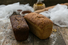 Close up view of fresh brown crispy loaf of bread lying on the wooden table sprinkled with flour. Royalty Free Stock Image