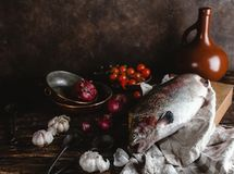 Close-up view of fresh fish on wooden cutting board and onions with garlic and cherry tomatoes. On rustic table Royalty Free Stock Photo